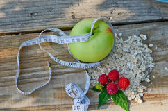 Green Apple wrapped with measuring tape next to the raspberry with leaves and a bunch of oatmeal. On wooden boards Stock Image