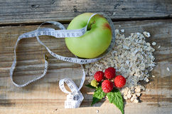 Green Apple wrapped with measuring tape next to the raspberry with leaves and a bunch of oatmeal. On wooden boards Royalty Free Stock Photos