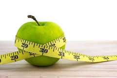 Green apple wrapped with measuring tape on wooden surface. Stock Photography