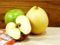 Green apple yellow chinese pear and red apple on wooden background Royalty Free Stock Photography