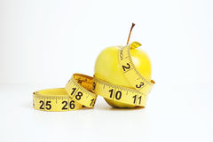 Green apple with yellow measuring tape Stock Photography
