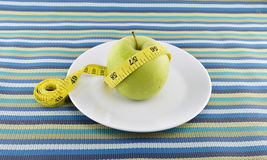 Green apple and yellow measuring tape concept for healthy diet a Stock Photography