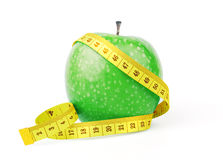 Green apple with yellow measuring tape Royalty Free Stock Images