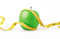 Green apple with yellow measuring tape Royalty Free Stock Photography