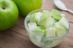 Green apple with yogurt in bowl Royalty Free Stock Image