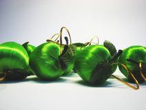 Green apples 18. Green satin Christmas apples on the grey background royalty free stock photo