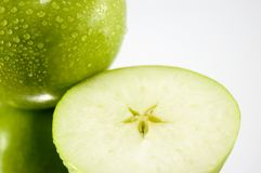 Green apples. First green apple with drops of watter and second half of green apple with the star in the middle. Put on mirror. Isolated Royalty Free Stock Photography