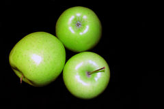 Green apples. Three green apples on black background Royalty Free Stock Image