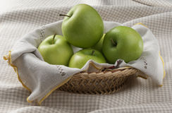 Green apples. Some green apples in the wicker on the tablecloth Stock Images