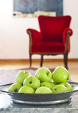 Green Apples. A plate full of green apples and red sofa in the background Royalty Free Stock Photo