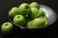 Green apples. In iron bowl on marble table royalty free stock image