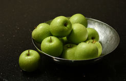 Green apples. On marble table with darkers lighting stock images