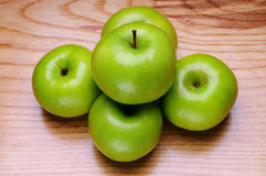 Green apples. On a wood background stock photos
