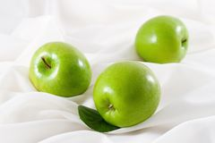 Green Apples. Tree green apple on white fabric background Royalty Free Stock Images