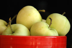 Green apples. In a red bawl Stock Photography