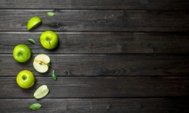Green apples and Apple slices. On a dark wooden background royalty free stock photos