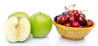 Green apples and a basket of cherries Stock Image