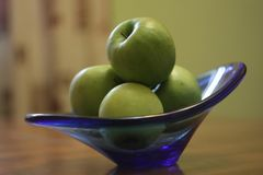 Green apples in a blue glass vasen stock images