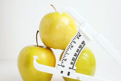 Green apples with body fat checker Stock Photography