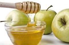 Green apples and a bowl of honey Royalty Free Stock Images