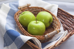 Green apples in the brown wicker basket. With a blue gingham cloth Royalty Free Stock Images