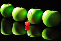 Green apples with cherry. On a black background Stock Photos