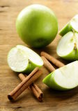 Green apples and cinnamon sticks Royalty Free Stock Photos