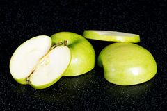Green apples cut into two. Stock Photos