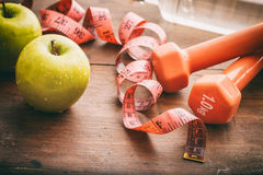 Green apples, dumbbells and measuring tape Stock Image