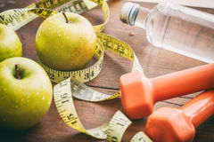 Green apples, dumbbells and measuring tape Royalty Free Stock Image