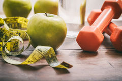 Green apples, dumbbells and measuring tape Stock Photography
