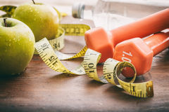 Green apples, dumbbells and measuring tape Royalty Free Stock Images