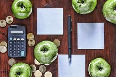 Concept: business, investment, enrichment, logistics, planning. Green apples, gold coins, calculator and paper for entries on the Royalty Free Stock Photo