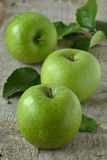 Green apples on gray background. Three green apples on a wooden gray background Stock Photo