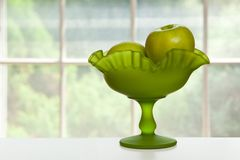 Green apples in green dish. Green granny smith apples in a glass green dish in front of a window Stock Images