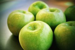 Green Apples. Grouped on a plate with cinematic post processing Stock Image