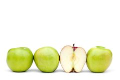 Green apples with an individual eaten red apple Stock Photo