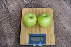 Green apples on kitchen scale. Green apple on kitchen scale  on wooden background.Dieting concept Royalty Free Stock Photo