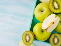 Green apples and kiwi on turquoise Royalty Free Stock Image