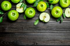 Green apples with leaves and Apple slices. On wooden background stock photo