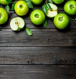 Green apples with leaves and Apple slices. On wooden background stock image