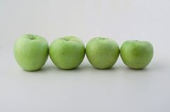Green apples in line. Four green apples in a line royalty free stock photography