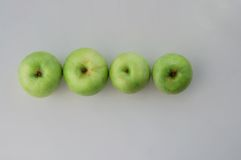Green apples in line. Four green apples in the line the view from the top stock photography