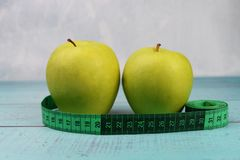 Green apples with measuring centimeter for weight control. And health and diet on a wooden background royalty free stock photos