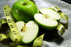 Green apples with measuring tap. Green cut & whole apples with measuring tap royalty free stock images