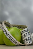Green apples and measuring tape Stock Images