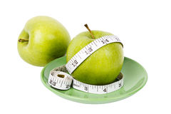 Green apples with measuring tape on green plate Stock Photo