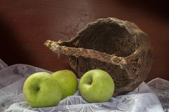 Green apples with old basket Royalty Free Stock Photo