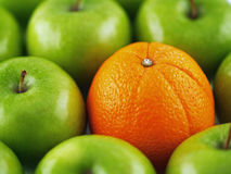 Green Apples and Orange. Background of green apples with a single Orange in the midst Stock Photography