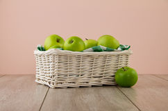Green apples on pink. A white wicker basket full of green apples, with emerald green gingham Stock Photography